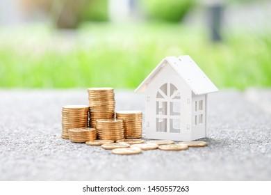 Modelo de casa de madera y pila de monedas. Concepto de inversión inmobiliaria.