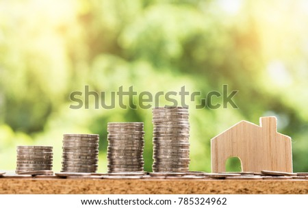 wooden house model and step of coins stacks with nature background, money, saving and investment or family planning concept, over sun flare silhouette tone.