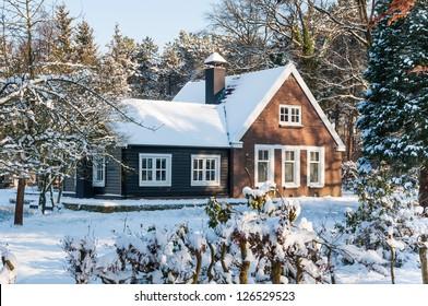 Holzhaus in einer Naturlandschaft, bedeckt mit frisch gefallenem Schnee.