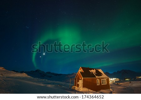 Wooden house and northern lights (aurora borealis) in Greenland