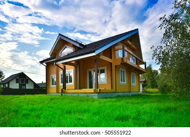 wooden house on green grass with blue sky background