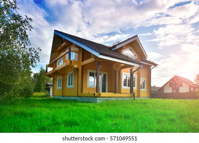 wooden house on green grass with blue sky background and the sun's rays
