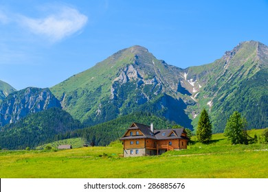 Wooden house on green meadow with Tatry Bielskie Mountains in background in summer, Slovakia
