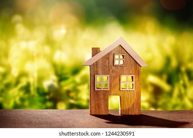 Wooden house on stone floor in front of nature background with bokeh