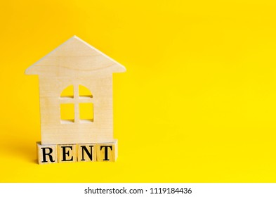 Wooden house on a yellow background with the inscription rent. Rental of property, apartments. services of a realtor. affordable housing, rental prices. place for text. copyspace