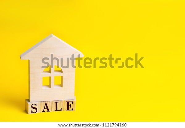 "wooden house on a yellow background with the inscription ""sale"". sale of property, home, real estate. affordable housing. place for text. copyspace"