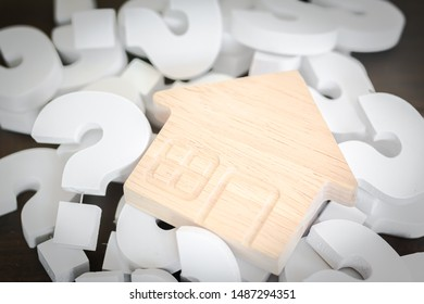 Wooden House over group of White Question mark , Problem concept