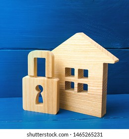 Wooden house with a padlock. Buying a home. House with a lock. Security and safety, collateral, loan for a mortgage. Confiscation of property for debts. Safety and alarm system.