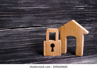 Wooden house with a padlock. House with a lock. Security and safety, collateral, loan for a mortgage. Confiscation of property for debts. Safety and alarm system. Buying a new home