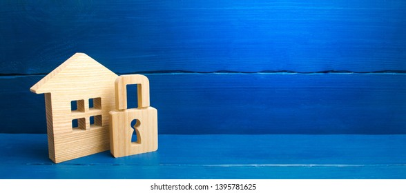 Wooden house with a padlock. House with a lock. Security and safety, collateral, loan for a mortgage. Confiscation of property for debts. Safety and alarm system. Buying a home. banner, place for text