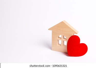 Wooden house with a red heart on a white background. Love nest, love relationships. Buying a house with a young family. Affordable housing. Family psychology, strong relations. Love and offspring