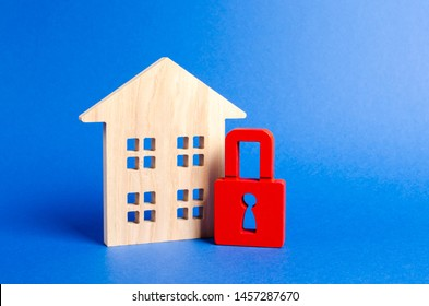 Wooden house and a red padlock. Security and safety. Confiscation for debts. alarm system. seizure of property. Protection of property rights. Unavailable and expensive real estate. house Insurance