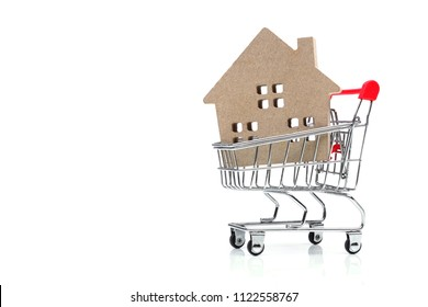 A wooden house in a shopping cart / Online house sale concept
