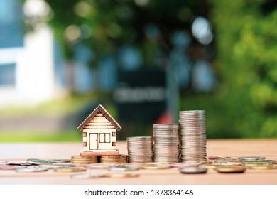Casa de madera y pila de monedas. Inversión inmobiliaria y ahorro de dinero para obtener propiedades.
