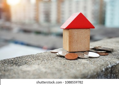 Wooden house and stacks of coins standing next ,Little wooden house made of toy blocks on beautiful blue and city background ,Real estate concept, Choose your best deal, saving money for real estate