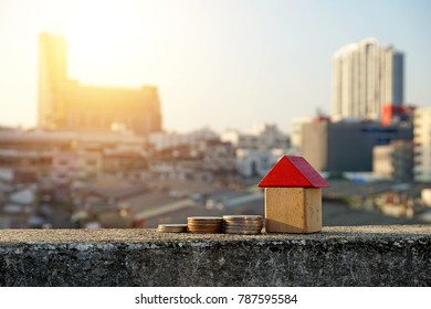 Wooden house and stacks of coins standing next ,Little wooden house made of toy blocks on beautiful blue and city background ,Real estate concept, Choose your best deal, Buying one of this houses