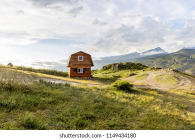 wooden house standing on a glade in the mountains