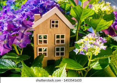 Wooden house stands between flowers and leaves