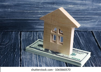 A wooden house stands on a stack of dolor banknotes. The concept of buying and selling immovability, rent of apartments. Credit and mortgage, affordable housing. Utilities payments