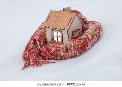 a wooden house stands in the snow, wrapped in a knitted scarf, the concept of a heating season, cold weather, a cozy and warm home for a family