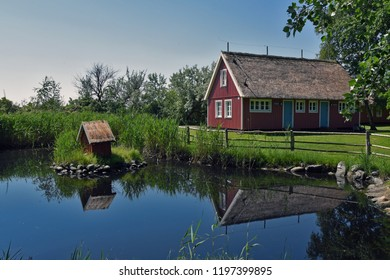 Wooden house with thatched roof by a pond with a duck house