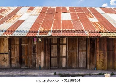 Holzhausdach, altthailändisches Holzhaus mit rosafarbenem Zinkdach
