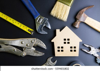 Wooden house toy and construction tools on black background with copy space.Real estate concept, New house concept, Finance loan business concept, Repair maintenance concept