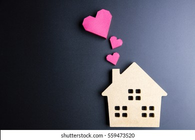 Wooden house toy and paper box red heart shape on black background with copy space.Real estate concept, New house concept, Love house concept, Finance loan business concept