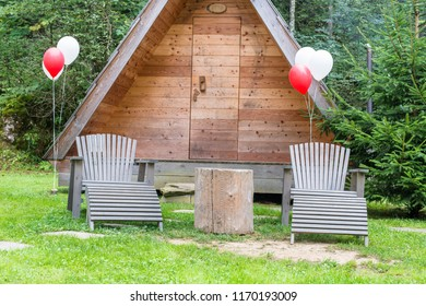 Wooden house with two chairs and heart balloons