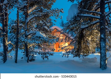 Wooden house with warm light in dark cold winter forest - Winter fairytale landscape