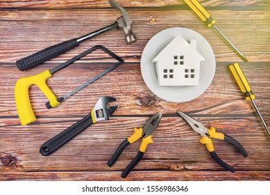 Wooden house in white dish and construction tools on woodden table background with copy space.Home Repair concept, Repair maintenance concept, Renovation concept