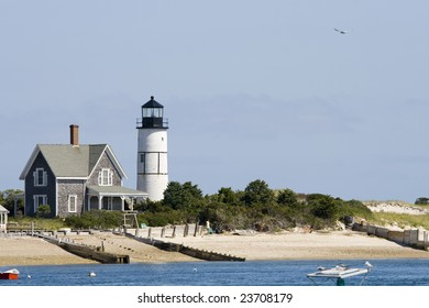Wooden house and white lighthouse at Cape Cod near Portland
