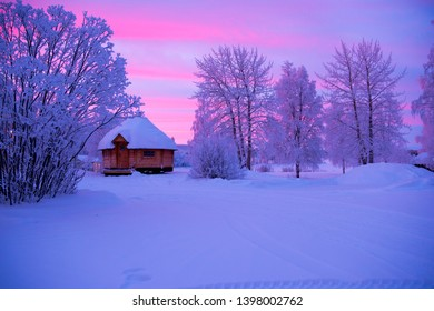 A wooden house in winter during sunrise