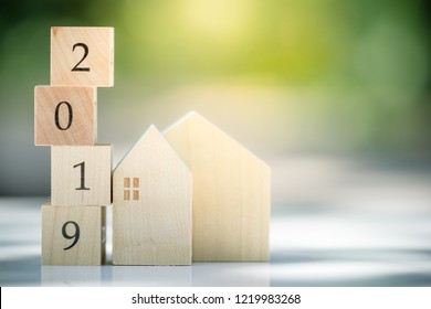 Wooden house with wood number 2019 and coins and copy space using as background business, new year, real estate, property concept.
