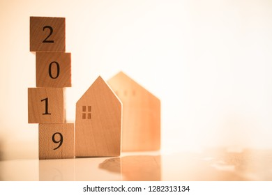 Wooden house with wood number 2019 on blurred city scape and copy space for text using as background business, new year, real estate, property concept