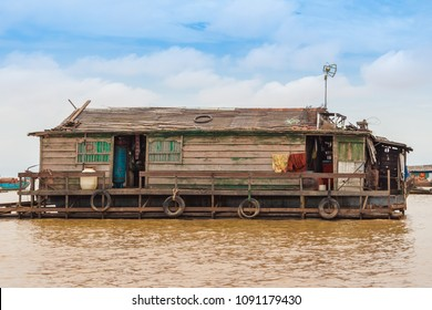 A wooden houseboat anchored in the floating village Chong Kneas on Tonle Sap Lake in Cambodia. The floating home has old tires as bumpers, an antenna, a wooden handrail and a clothesline.