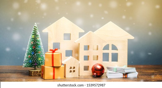 Wooden houses, Christmas tree, money and gifts. Christmas Sale of Real Estate. New Year discounts for buying housing. Purchase apartments at a low price. Holiday discounts. Favorable prices