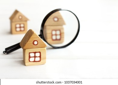 Wooden houses and magnifying glass for inspection / thorough study of real estate offers