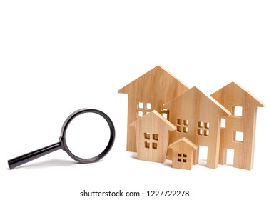 Wooden houses and magnifying glass on a white isolated background. Home search concept. Affordable housing. Rent apartment or house. Real estate concept. Real estate appraisal. property