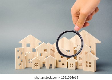 Wooden houses and magnifying glass. Property valuation. Home appraisal. Choice of location for the construction. House searching concept. Search for housing and apartments. Real estate