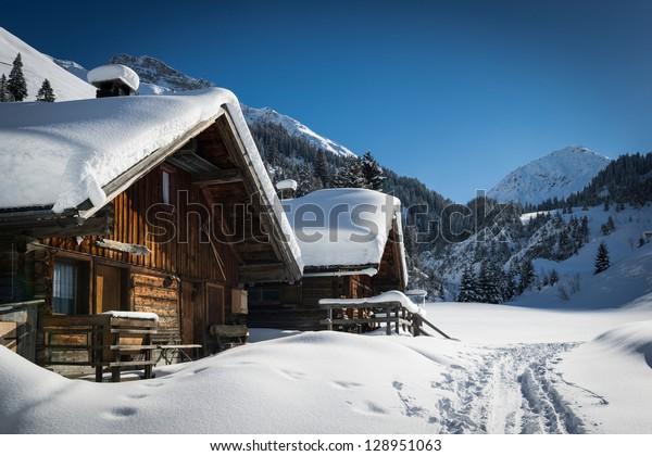 Holzhäuser auf den österreichischen Bergen im Winter mit viel Schnee