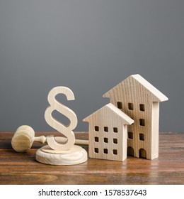 Wooden houses and paragraph figurine with judge hammer. Litigation in housing and real estate disputes. Norms and rules for construction, maintenance. Encouraging green and energy-saving technologies