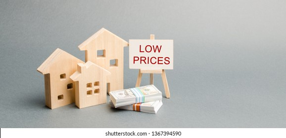 Wooden houses and a poster with the words Low Prices. The concept of reducing the value of real estate. Lower mortgage interest rates. Falling prices for rental housing and apartments. Home sales