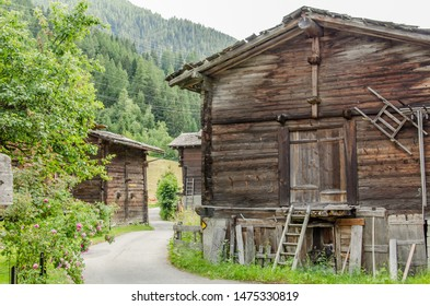 Wooden houses and sheds in rural village in Swiss alps in Valais valley on a summer day