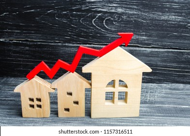 Wooden houses stand in a row from small to large with a red arrow up. concept of high demand for real estate. increase energy efficiency of housing. rise in house prices. property. population growth