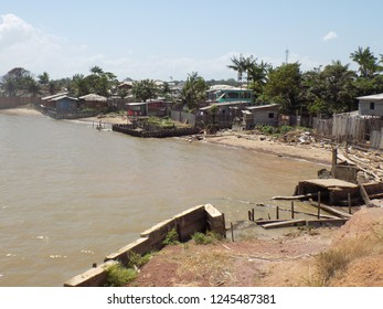 Wooden houses and trees on the banks of the Amazon River, in Macapa