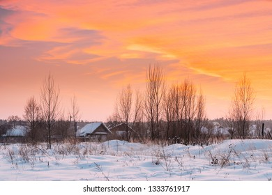 Wooden Houses At Winter Sunset Dawn Sunrise Time. Village In Belarus