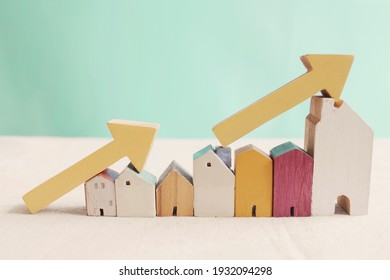 Wooden houses with yellow arrows up. housing boom, property market growing, high demand for real estate, house prices rising concept - Shutterstock ID 1932094298