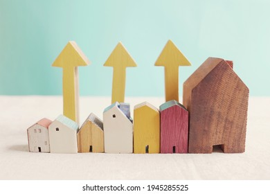 Wooden houses with yellow arrows up. housing boom, property market growing, high demand for real estate, house prices rising concept - Shutterstock ID 1945285525