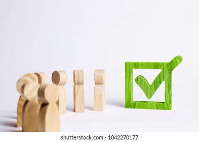 wooden human figures stand together next to a tick in the box. The concept of elections and social technologies. Volunteers, parties, candidates, electorates. Selective focus.